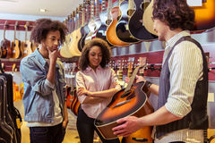 People in musical shop. Beautiful young Afro-American couple choosing a guitar while standing in a musical shop. Caucasian men holding a guitar Royalty Free Stock Photos