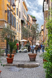People on the narrow picturesque street in Rome, Italy Stock Photo