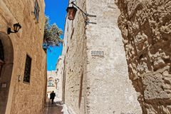People at Narrow street with lantern in Mdina. Malta Royalty Free Stock Image