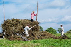 People in national costumes work in the field on Kizhi Royalty Free Stock Image
