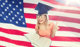 Student woman in mortarboard with encyclopedia. People, national education, knowledge and graduation concept - smiling young student woman in mortarboard and stock photos