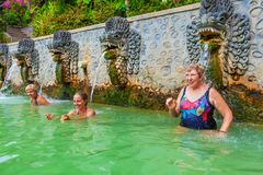People in natural hot spring Air Panas Banjar on Bali. 3 generations of women in thermal bath, relaxing under flowing water stream of shower in traditional stock photography