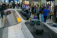 People near the Baggage carousel at the Schiphol Airport, Amsterdam. AMSTERDAM, THE NETHERLANDS - OCTOBER 4, 2013: Baggage carousel at the Amsterdam Airport Stock Photo