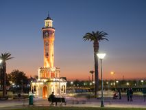 People near clock tower of Izmir at evening , Turkey. Night place with clocktower and palms in Izmir Stock Photography