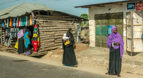 People near a clozing store by road, Zanzibar Stock Images