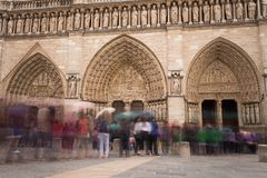 People near the entry to Notre-Dame de Paris, famous ancient catholic cathedral on a cloudy day. Touristic historical. And architectural landmark in France Royalty Free Stock Images