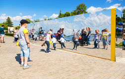 People near the giant stainless steel mirror at the city park in Royalty Free Stock Photo