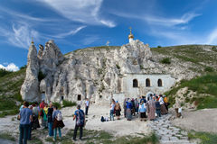 People near Orthodox cathedral carved out of natural rock in Divn Stock Images