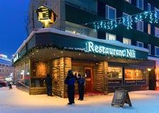 People near traditional restaurant in winter Rovaniemi illuminated at night stock image