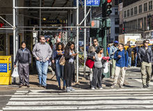 People near Wall street in Manhattan cross the street at white t Stock Images