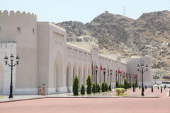 People near wall of Sultan's Palace in Oman. Bus and cars Stock Photos