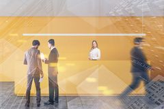 People near yellow office reception. Business people discussing documents and walking near yellow office reception desk with blonde secretary. Business lifestyle royalty free stock photo