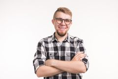 People, nerd and education concept - Smiling handsome student man in plaid shirt, crossed arms, over white background.  stock photography