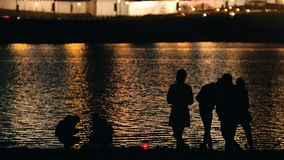 People at night city near river - night lights background. Telephoto stock footage