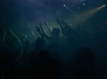 People in the night club. People dancing in the fog highlighted with night club lighting equipment Royalty Free Stock Image