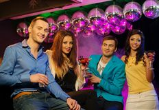 People at night club. Group of cheerful young friends sitting with drinks at night club Stock Photography