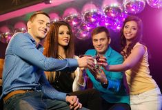 People at night club. Group of cheerful young friends sitting with drinks at night club Stock Images