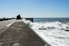 People observing waves in Foz do Douro royalty free stock photography