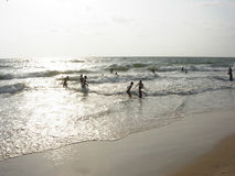 People in the ocean surf. On a sandy beach in the afternoon Royalty Free Stock Photography