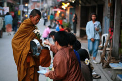People offer food and flower to monk Royalty Free Stock Image