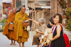 People offer sticky rice to Buddhist monks in the morning in Chiang Khan, Thailand. Royalty Free Stock Image