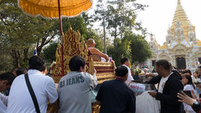 people offering food and items to a buddhist monk and being bles Stock Images