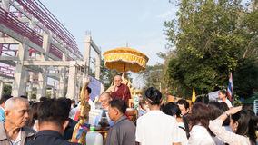 people offering food and items to a buddhist monk and being bles Stock Photos