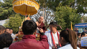 people offering food and items to a buddhist monk and being bles Royalty Free Stock Photo