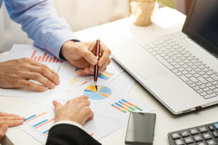 People at office analyzing business financial graph reports. On table stock photo