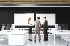 People in office with black walls and two posters Royalty Free Stock Image