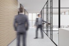 People in office hall with wooden and glass walls Stock Photography