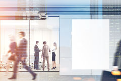 People in an office lobby, mockup double. Company employee sare walking in a modern office lobby with glass and gray walls, a concrete floor and a large vertical Royalty Free Stock Photos