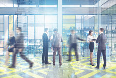 People in an office lobby with yellow and gray floor pattern, a meeting room and an open space. Royalty Free Stock Image