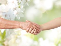 Close up of senior and young woman holding hands. People, old age and generation concept - close up of senior and young woman holding hands over natural spring Stock Photos