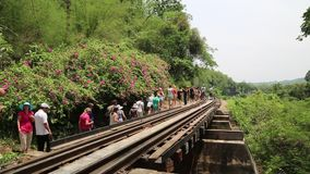 People on old railroad near Kwai river in Thailand stock video footage