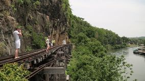 People on old railroad near Kwai river in Thailand. THAILAND, KANCHANABURI PROVINCE, APRIL 5, 2014: People on old railroad near Kwai river in Thailand stock footage