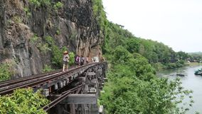 People on old railroad near Kwai river in Thailand. THAILAND, KANCHANABURI PROVINCE, APRIL 5, 2014: People on old railroad near Kwai river in Thailand stock video footage