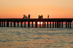 People on the old sea pier during sunset Royalty Free Stock Photo