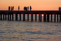 People on the old sea pier at sunset Stock Images
