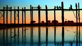 People on the old teak bridge. Burma, Mandalay, sunset Royalty Free Stock Photos