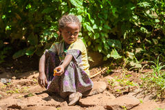 People in OMO, ETHIOPIA. OMO, ETHIOPIA - SEPTEMBER 20, 2011: Unidentified Ethiopian beautiful little girls sits on the ground and takes a rest. People in Stock Photography
