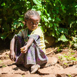 People in OMO, ETHIOPIA. OMO, ETHIOPIA - SEPTEMBER 20, 2011: Unidentified Ethiopian beautiful little girls sits on the ground and takes a rest. People in Royalty Free Stock Photo
