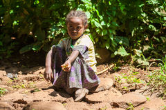 People in OMO, ETHIOPIA. OMO, ETHIOPIA - SEPTEMBER 20, 2011: Unidentified Ethiopian beautiful little girls sits on the ground and takes a rest. People in Royalty Free Stock Photography