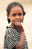 People in OMO, ETHIOPIA. OMO, ETHIOPIA - SEPTEMBER 22, 2011: Unidentified Ethiopian cute little girl with stripe shirt. People in Ethiopia suffer of poverty due Stock Image