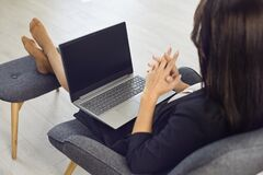Free People Online.A Businesswoman With A Laptop Online In A Chair Comfortably Relaxing Looks At The Monitor In The Room Stock Photography - 179835242