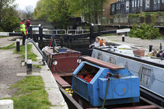 People opening the gate for a boat passing a barrage on the way through the Regent Canal Royalty Free Stock Image