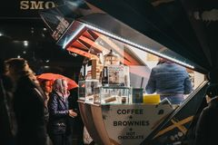 People ordering drinks from a coffee and brownies stall in Canary Wharf, London, UK royalty free stock photography