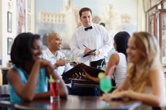 People ordering meal to waiter in restaurant Stock Photos