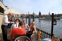People in outdoor cafe on the Vltava river waterfront in Prague, Czech Republic. stock photos