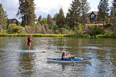 People Paddle Boarding And Canoeing In River. A woman stand up paddle boarding and young girl canoeing enjoying a nice day in the Deschutes River royalty free stock photography